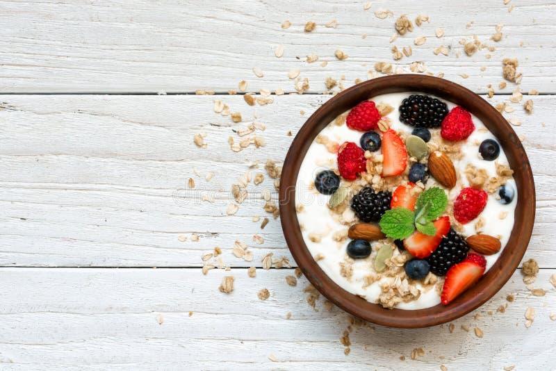 Bol de yaourt grec avec la granola, l'avoine, les baies et les écrous pour le petit déjeuner sain photo libre de droits