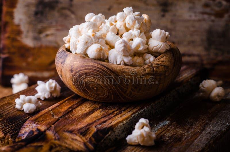 Bol en bois complètement de maïs éclaté doux dans la cuvette en bois de vintage sur la table rustique Type de cru Foyer sélectif photo libre de droits