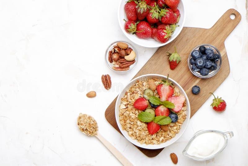 Bol en céramique de granola, ingrédients assortis sur la table Petit déjeuner nutritif sain avec du yaourt de vegan, les fruits c photographie stock