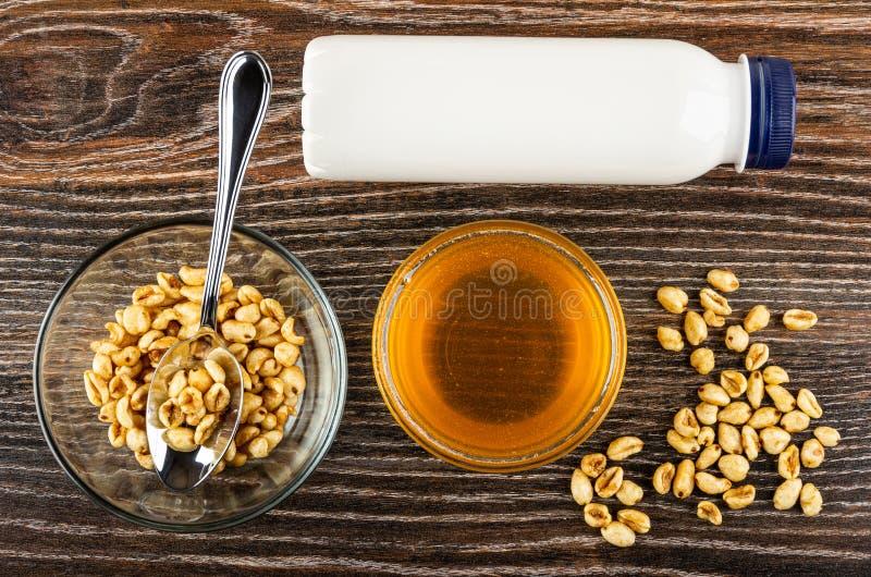 Bol en verre avec du blé soufflé, cuillère, bouteille de yaourt, miel, blé soufflé dispersé sur la table Vue sup?rieure photos libres de droits