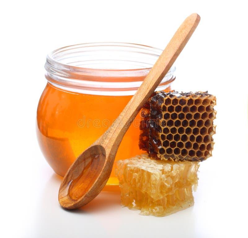Bol en verre avec du miel et le peigne de tranche images stock