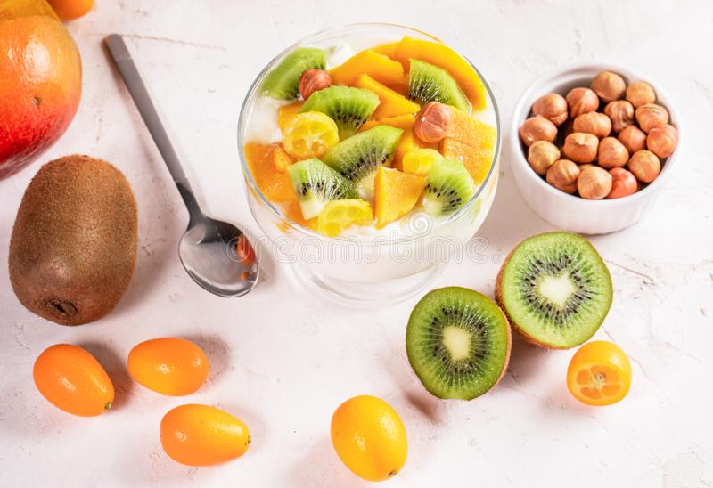 Bol en verre avec du yaourt, et fruits, cuillère métallique et cuvette d'écrous sur whitetable images libres de droits