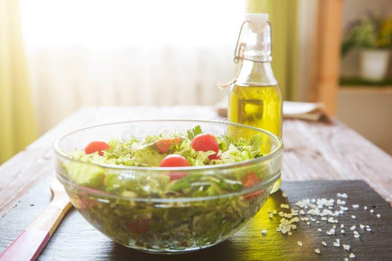Bol en verre de salade verte fraîche sur la surface en pierre noire sur le fond en bois sur une cuisine rustique photos stock