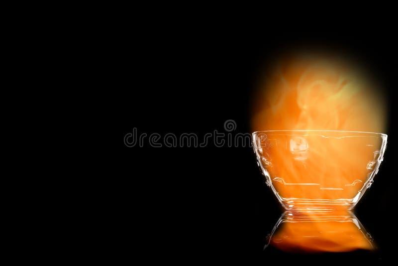 Bol en verre vide d'en dans les flammes du feu image stock