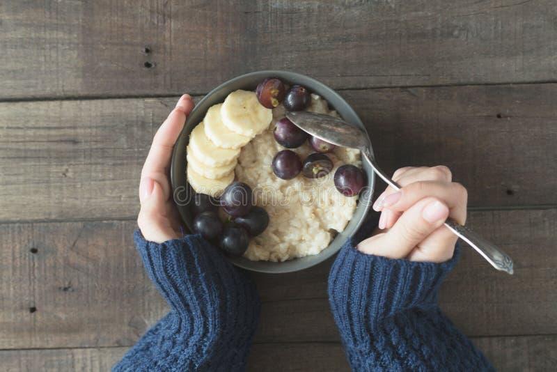 Bol gris de petit déjeuner sain avec le gruau et les fruits de farine d'avoine chez des mains du ` s des femmes Concept de nourri photos stock