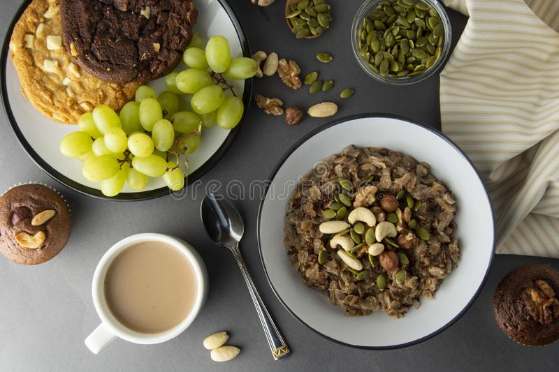 Bol sain de petit déjeuner Farine d'avoine avec des écrous - noix, graines de chia, graines de citrouille, miel et fruits frais,  photo stock