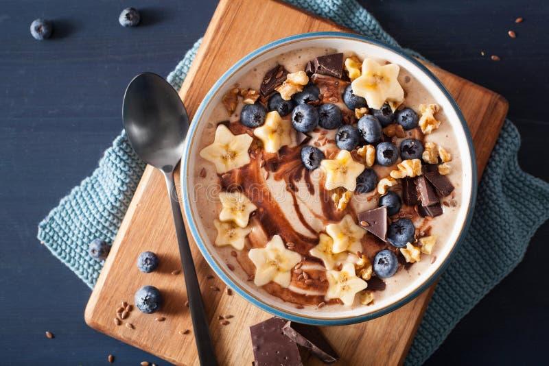 Bol sain de smoothie de banane avec des noix de chocolat de myrtille images libres de droits