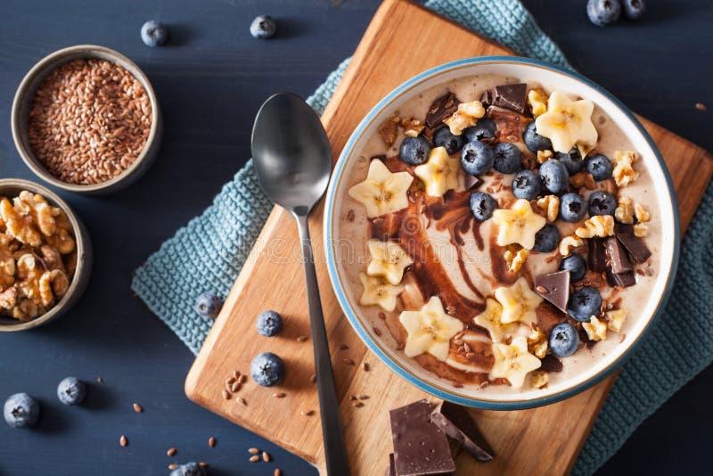 Bol sain de smoothie de banane avec des noix de chocolat de myrtille images stock