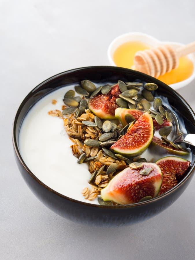 Bol sain de yaourt de petit déjeuner avec la granola et la figue image stock