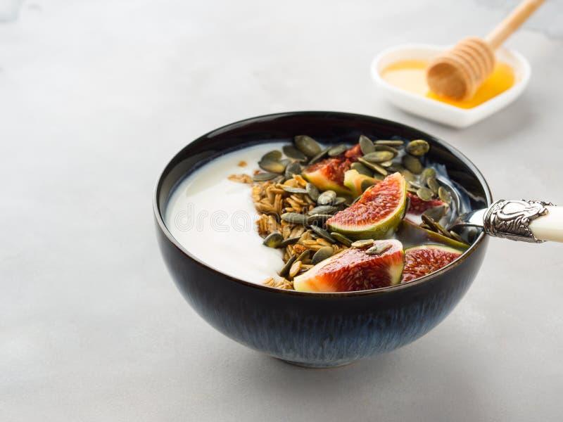 Bol sain de yaourt de petit déjeuner avec la granola et la figue photo stock