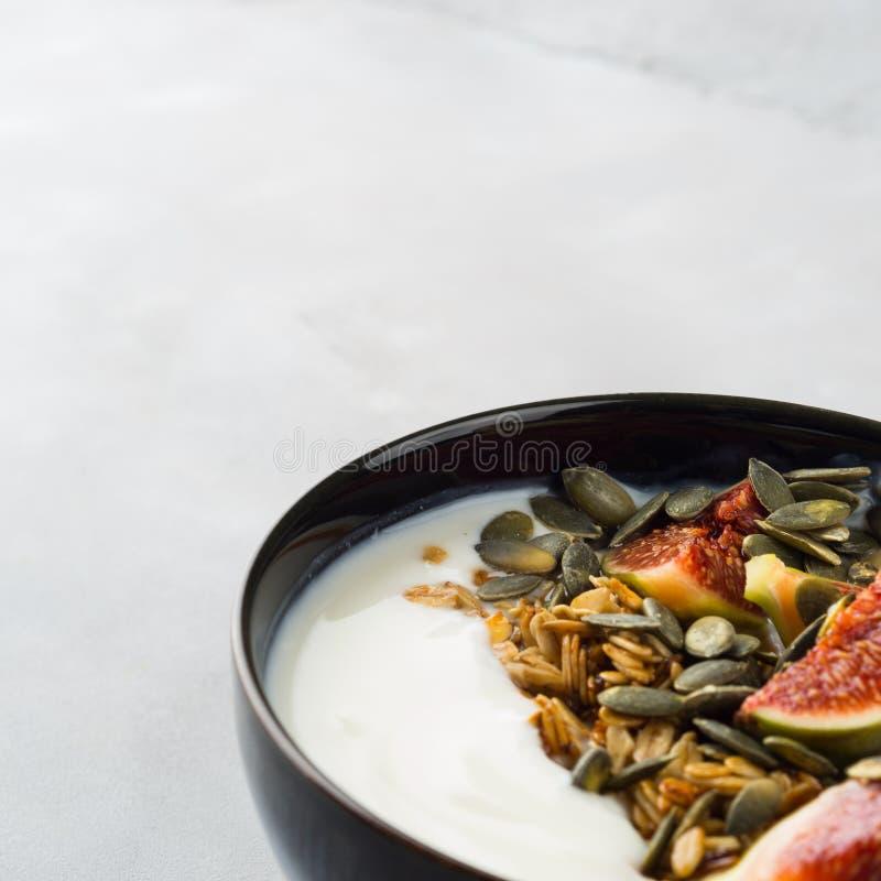Bol sain de yaourt de petit déjeuner avec la granola et la figue photos libres de droits