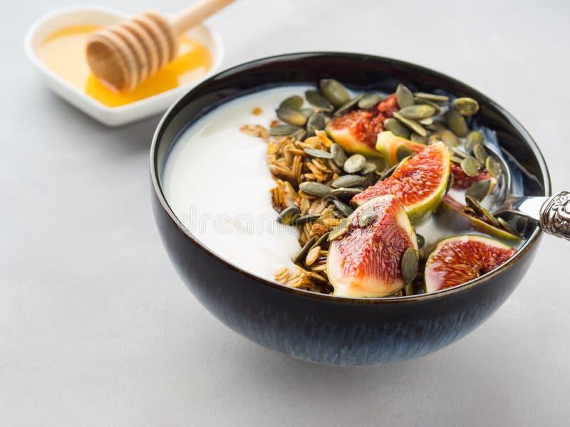 Bol sain de yaourt de petit déjeuner avec la granola et la figue photo libre de droits