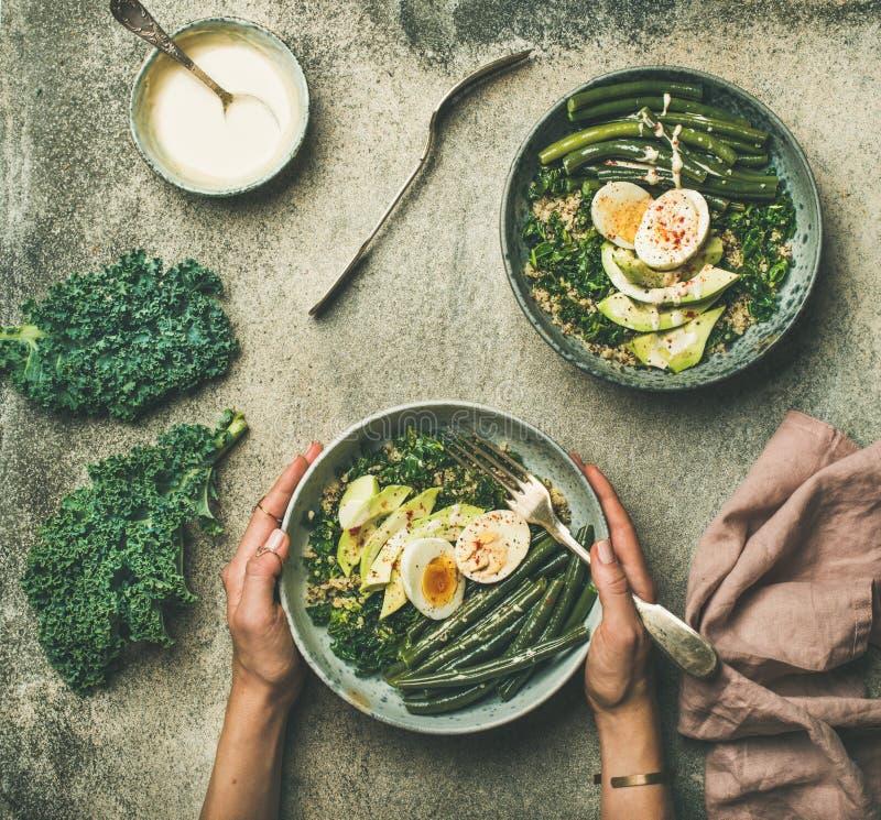 Bol végétarien sain de petit déjeuner d'oeufs de quinoa dans des mains femelles images stock