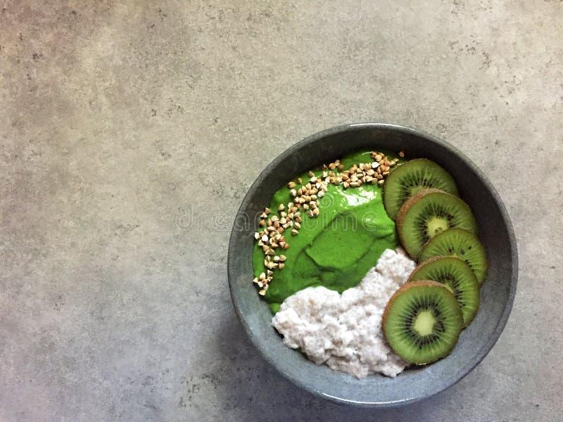 Bol vert de smoothie avec du sarrasin, le kiwi et le pudding de chia photographie stock libre de droits