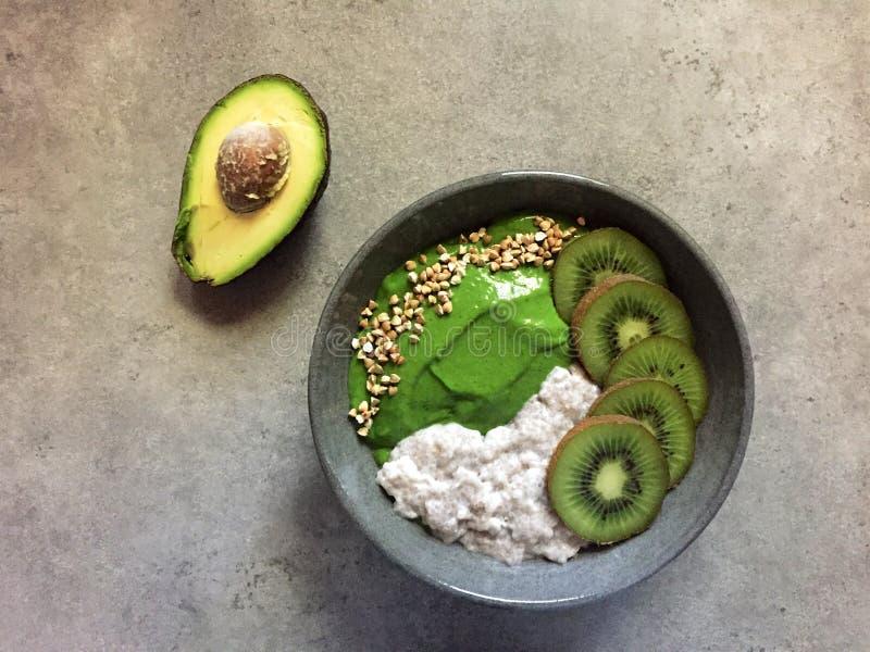 Bol vert de smoothie avec du sarrasin, le kiwi et le pudding de chia images stock