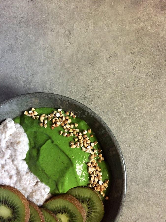 Bol vert de smoothie avec du sarrasin, le kiwi et le pudding de chia photos libres de droits