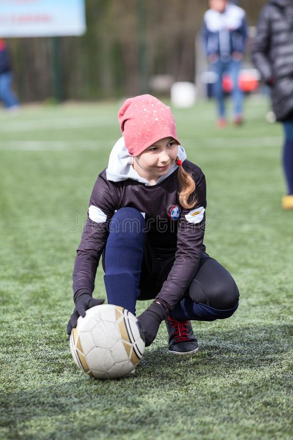 Bola adolescente de la tenencia del futbolista de la muchacha de la edad con las manos mientras que se sienta en un campo verde a imagenes de archivo