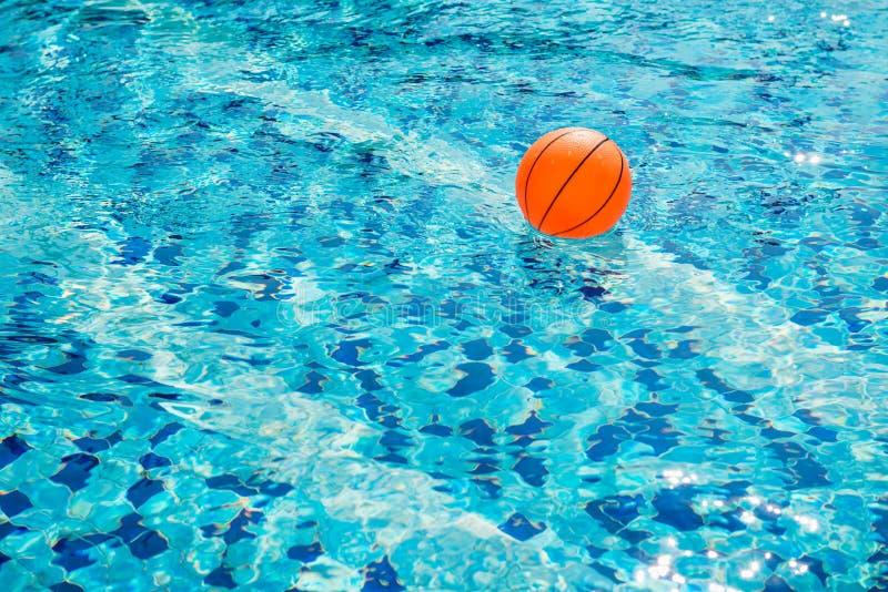 Bola alaranjada na água na piscina azul imagem de stock royalty free