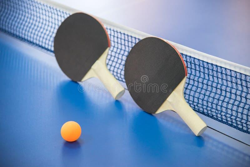 Bola alaranjada para o tênis de mesa e as duas raquetes do co vermelho e preto fotos de stock