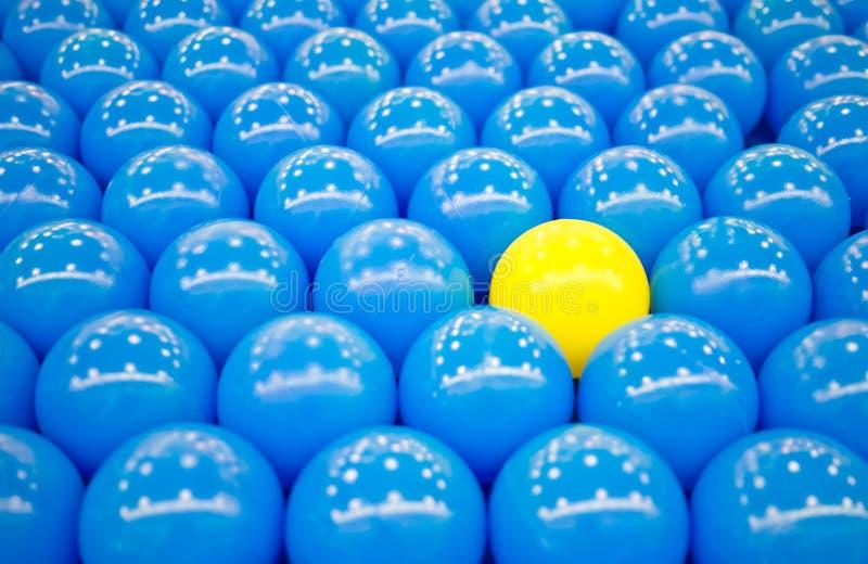 Bola amarilla única entre bolas azules imagen de archivo