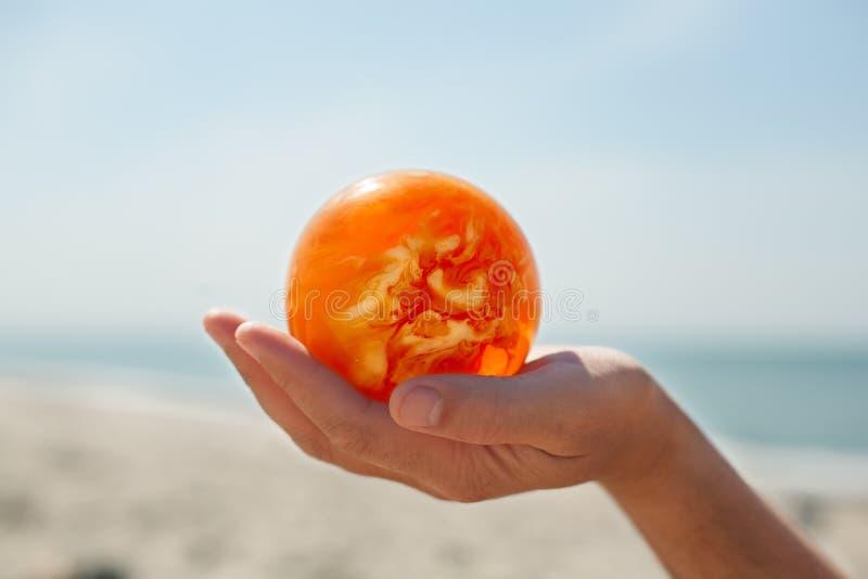 Bola ambarina que lleva a cabo el fondo ascendente cercano del mar Báltico de la mano imágenes de archivo libres de regalías