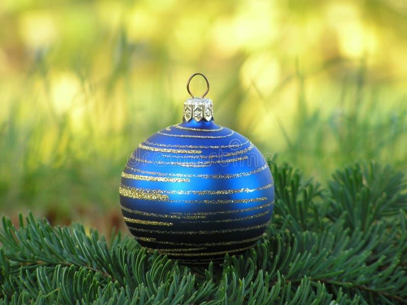 Bola azul de la Navidad con remolinos de oro en hierba verde fotos de archivo libres de regalías