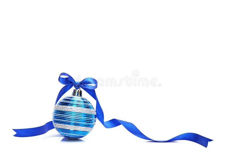 Bola azul do Natal com curva da fita no fundo branco imagem de stock
