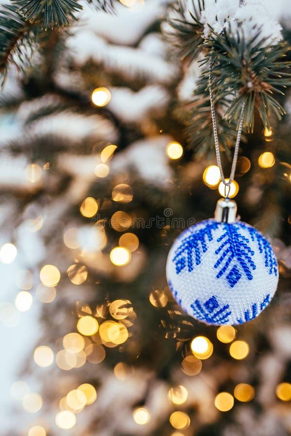 Bola azul do White Christmas no fim do ramo de árvore do abeto acima do bokeh claro amarelo dourado fotos de stock royalty free