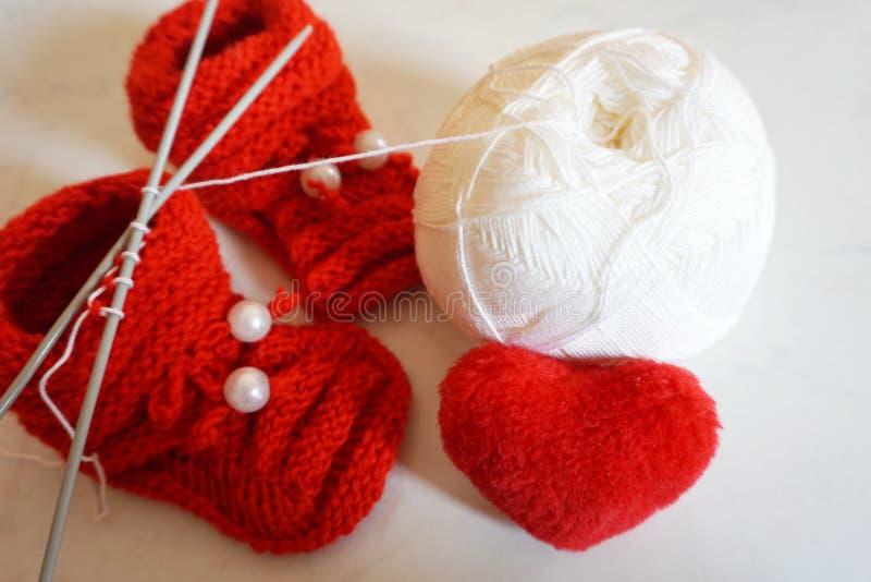 Bola blanca de lanas que hacen punto y de zapatos de bebé hechos punto fotos de archivo