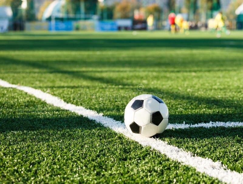 Bola blanco y negro clásica del fútbol en la hierba verde del campo Partido de fútbol, entrenamiento, concepto de la afición imágenes de archivo libres de regalías