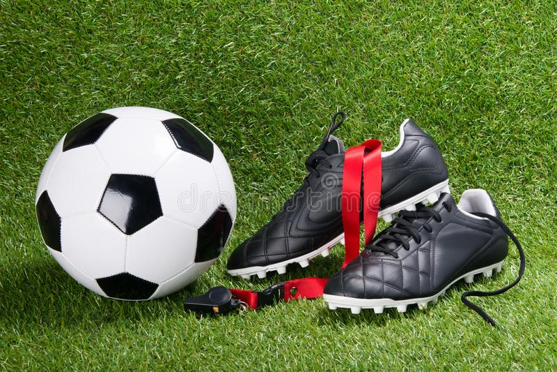 Bola, botas e assobio de futebol para o árbitro, na perspectiva da grama foto de stock