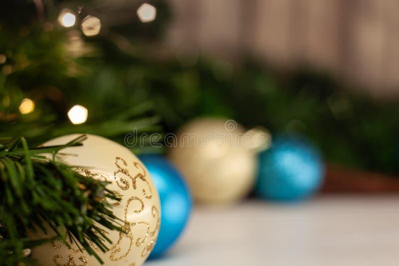 Bola branca do brinquedo do Natal com um teste padrão brilhante ao lado de uma bola azul em uma tabela clara fotografia de stock