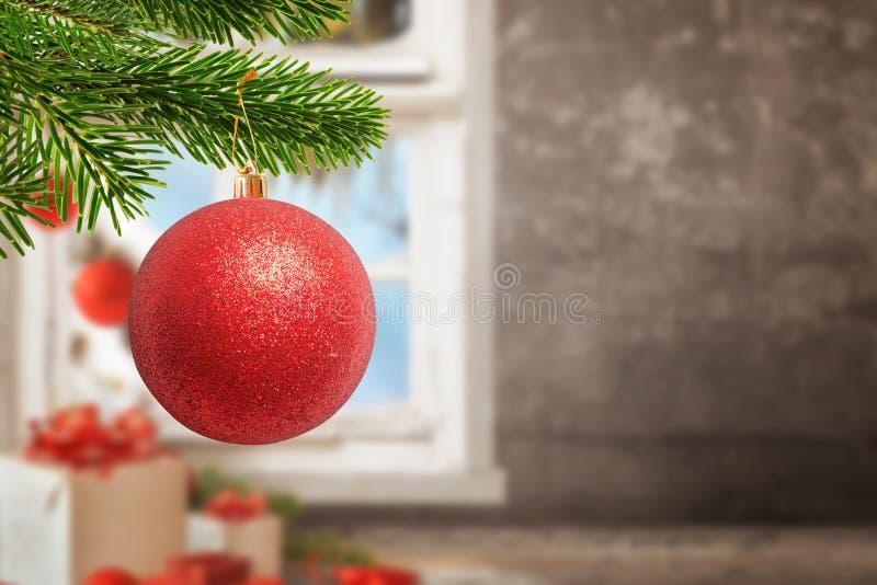 Bola brillante roja de la Navidad en árbol Regalos, decoraciones, pared y ventana en fondo con el espacio de la copia imagenes de archivo