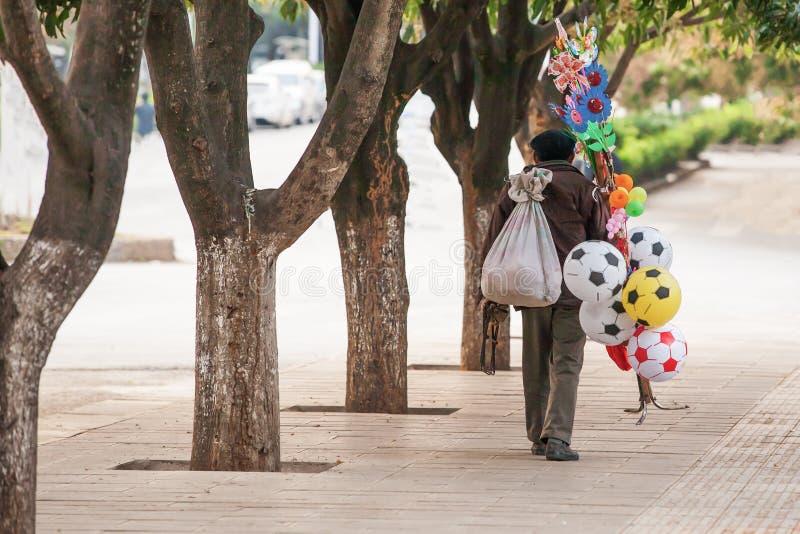 Bola chinesa do vendedor do vendedor ambulante do ancião e outros brinquedos no fotografia de stock