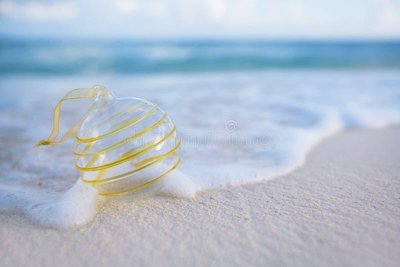 Bola clara de vidro de natal na praia fotos de stock royalty free