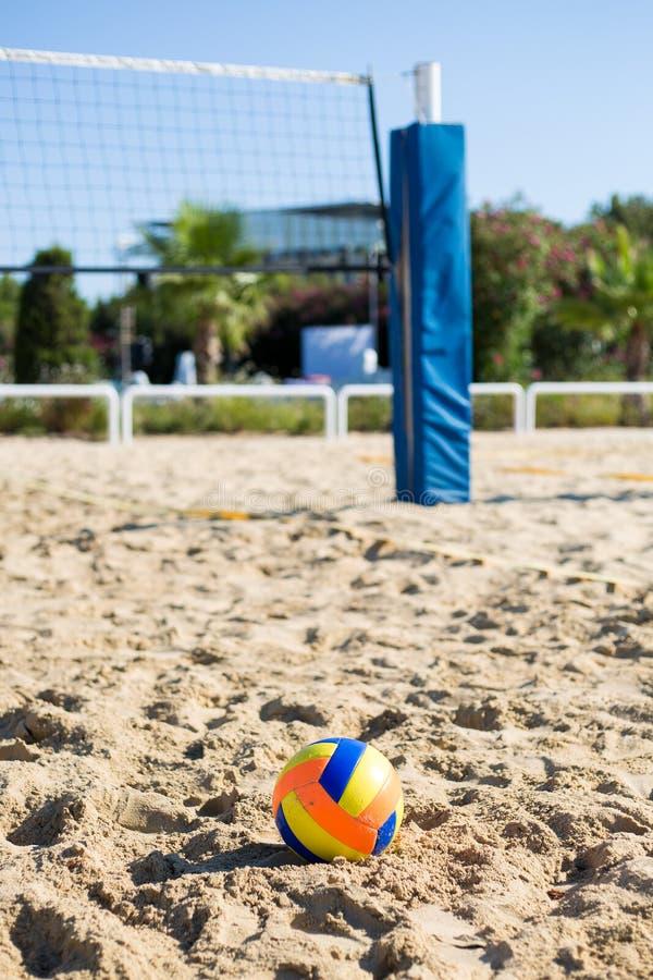 Bola colorida voleibol na areia no fundo da grade do jogo foto de stock royalty free