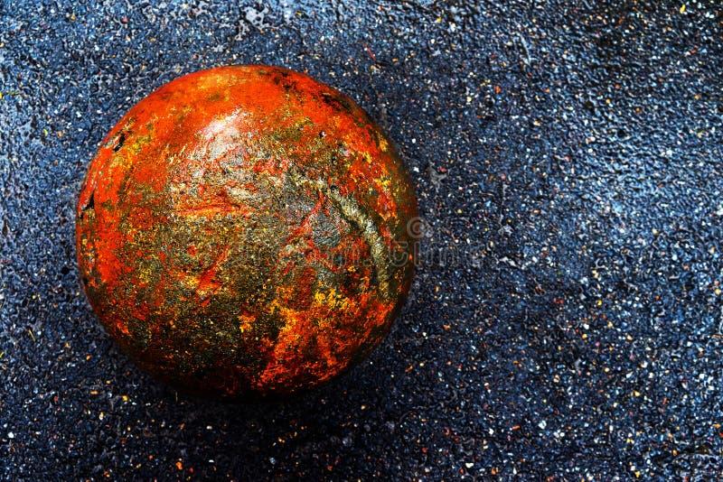 Bola concreta oxidada en el asfalto oscuro mojado imagenes de archivo