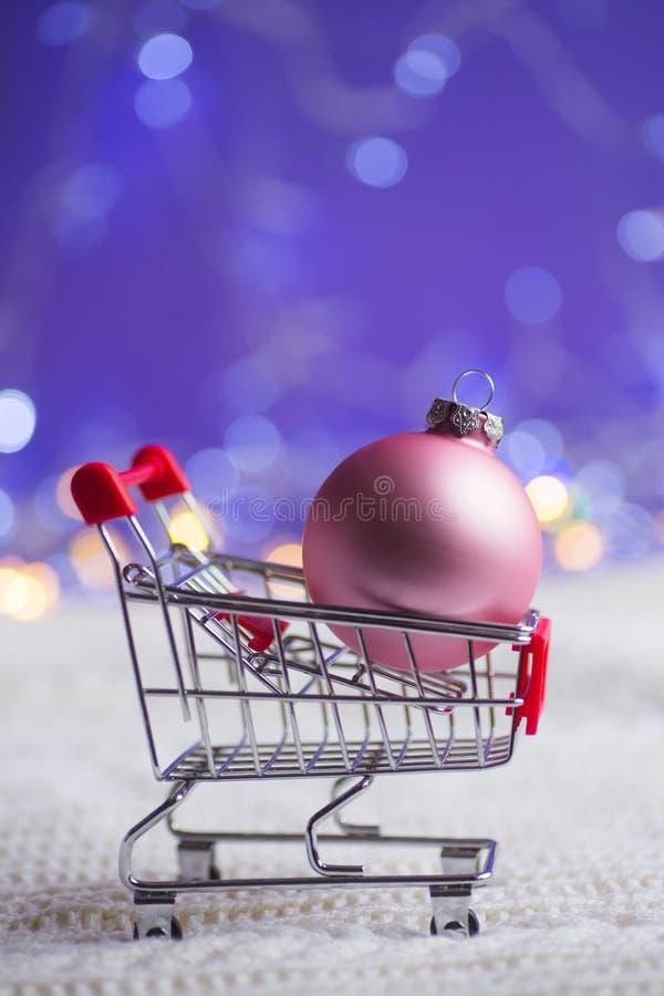 Bola cor-de-rosa do Natal no trole do supermercado pequeno na tela feita malha branca com luzes da festão no fundo roxo do bokeh  fotografia de stock royalty free
