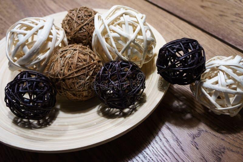 A bola de bambu é a cor 3 branca, preta e marrom na madeira estratificada do prato com a tabela de madeira marrom fotografia de stock