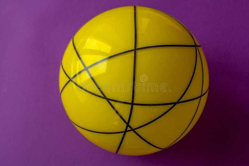 Bola de cristal amarilla grande en un fondo violeta Todavía vida de la bola amarilla rayada en la tabla violeta brillante fotos de archivo