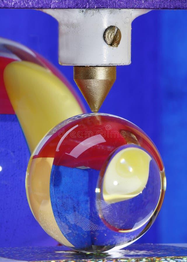 Bola de cristal bajo la prensa de la máquina imágenes de archivo libres de regalías