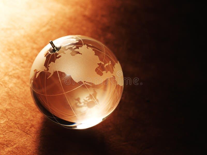 Bola de cristal con una imagen de un mapa del mundo en el papel del vintage fotos de archivo libres de regalías
