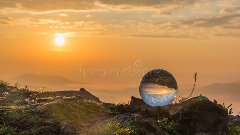 Bola de cristal en la roca que duplica la salida del sol imagen de archivo
