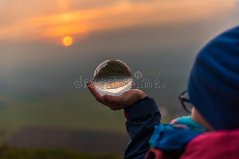 Bola de cristal en mano del ` s de la muchacha durante puesta del sol imagenes de archivo