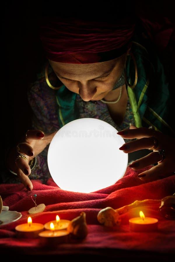 A bola de cristal para dizer da fortuna e as mãos da fortuna aciganada dizem foto de stock