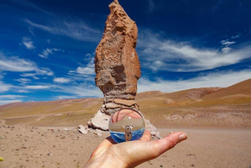 Bola de cristal que se sostiene derecha cerca de los monjes de Pacana imagen de archivo