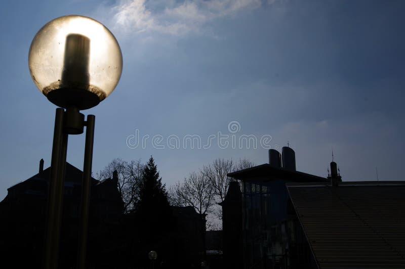 Bola de cristal de una lámpara de calle moderna con el sol detrás de él imagen de archivo libre de regalías