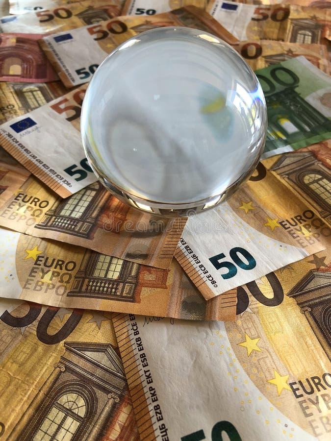 Bola de cristal y billetes de banco euro de la denominación grande imagenes de archivo