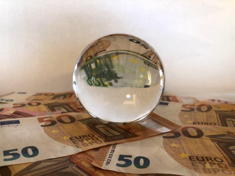 Bola de cristal y billetes de banco euro de la denominación grande fotos de archivo