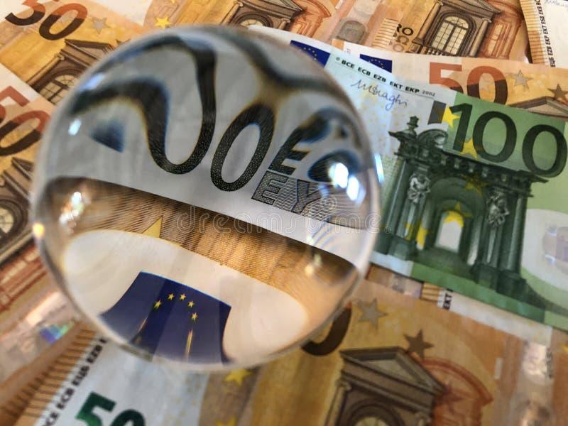 Bola de cristal y billetes de banco euro de la denominación grande imagen de archivo libre de regalías